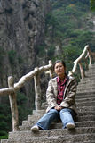 Woman sitting on steep steps. Chinese woman sitting on steep steps which are part of a mountain path Stock Image