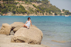 Woman Sitting on Stone Stock Images