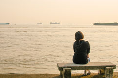 Woman sitting on a stone bench Royalty Free Stock Photo