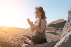 Woman sitting on stone in lotus pose and listening to music stock image