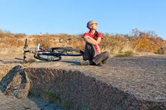 Woman sitting on a stone next to mountain bike relaxing and enj Stock Photography