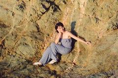 Woman Sitting on Stone Stock Photography