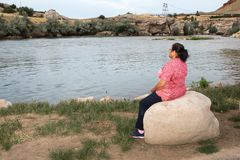Woman sitting on a stone by the river Stock Photos