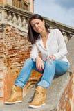 Woman sitting on stone staircase railing Stock Photo
