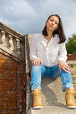 Woman sitting on stone staircase railing Stock Image