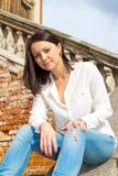 Woman sitting on stone staircase railing Royalty Free Stock Photo