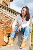 Woman sitting on stone staircase railing Stock Images