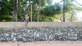 Woman on beach looking into mirror. Woman sitting on stone wall at beach looking into mirror with trees behind her stock image