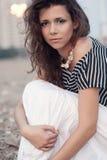Woman sitting on stones. Beautiful brunette  woman wearing striped blouse portrait sitting Royalty Free Stock Photography