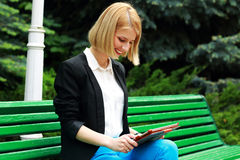 Woman sitting on the street bench Stock Image