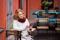 Woman is looking at phone. Woman is sitting in an street cafe and looking at phone Royalty Free Stock Images