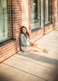 Woman sitting on street and leaning against brick wall Royalty Free Stock Image
