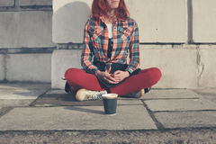Woman sitting in street with paper cup Stock Photography