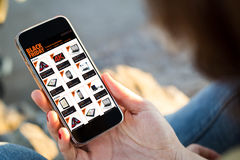 Woman sitting in the street shopping online with the smartphone Royalty Free Stock Photos