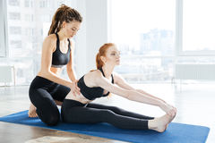Woman sitting and stretching with her coach Stock Photography