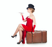 A woman sitting on a suitcase Stock Photo