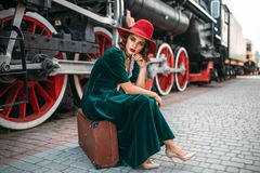 Woman sitting on suitcase against steam train. Young old-fashioned woman sitting on suitcase against vintage steam train, red wheels closeup. Old locomotive Stock Image
