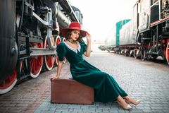 Woman sitting on suitcase against steam train Royalty Free Stock Photography