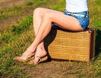 Woman sitting on suitcase Stock Photography
