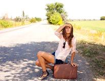 Woman sitting on a suitcase by a countryside road Royalty Free Stock Images