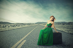 Woman sitting on suitcase on countryside road waiting for ride Stock Photos