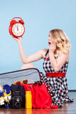 Woman sitting with suitcase holding old clock. Time for travel, being late concept. Terryfied woman sitting on floor with messy packed suitcase holding big red royalty free stock photo