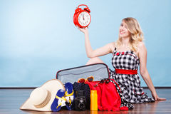 Woman sitting with suitcase holding old clock. Time for travel concept. Happy woman sitting on floor with messy packed suitcase holding big red old clock royalty free stock images