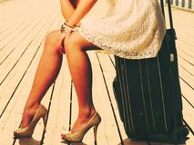 Woman sitting on suitcase, pier in background. Travel, packing, journey concept. Woman wearing white short dress sitting on suitcase thinking about adventure royalty free stock photo
