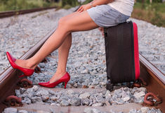 Woman sitting on suitcase in railway. Woman legs in red high heel shoes and sitting on suitcase in railway Royalty Free Stock Images