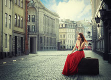 Woman sitting on suitcase talking on phone on quiet old town street Stock Images