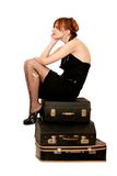 Woman sitting on suitcases Stock Images