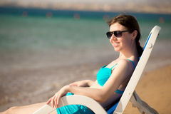 Woman sitting on sun deckchair Royalty Free Stock Image