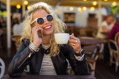 Woman sitting with sun glasses and talking on the phone Royalty Free Stock Image