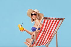 Woman sitting in a sun lounger and holding a cocktail. Young blond woman sitting in a sun lounger and holding an orange cocktail on blue background stock image
