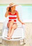 Woman sitting on sunbed and looking on copy space Stock Image