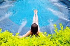 Woman sitting in swimming pool stock photo
