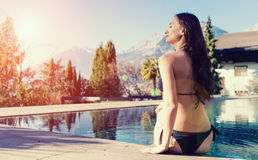 Woman sitting at swimming pool in Alp mountains Royalty Free Stock Images