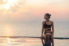Woman is sitting at the swimming pool on sunset Royalty Free Stock Images