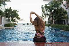 Woman sitting on swimming pool Royalty Free Stock Photography