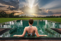 Woman sitting in swimming pool. Vacation lifestyle scene of young woman sitting in swimming pool in morning time with sunset landscape view in blurry background Royalty Free Stock Photography