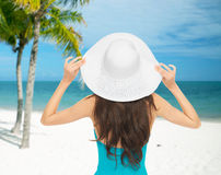 Woman sitting in swimsuit with hat Stock Images