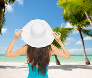 Woman sitting in swimsuit with hat Royalty Free Stock Image