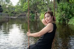 Woman sitting on a swing along the stream Swing your feet through the water slowly and happily royalty free stock photography