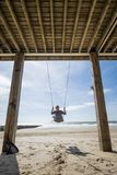 Woman is sitting in a swing at the beach royalty free stock photo