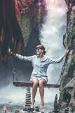 Woman Sitting on Swing Chair With Waterfalls Background stock photography