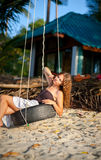 Woman sitting on the swing on paradise beach Royalty Free Stock Image