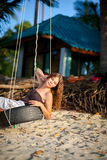 Woman sitting on the swing on paradise beach Royalty Free Stock Images