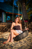 Woman sitting on the swing on paradise beach Stock Photos