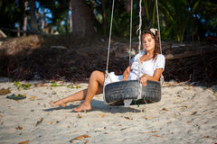 Woman sitting on the swing at paradise beach Stock Photography
