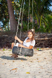 Woman sitting on the swing at paradise beach Royalty Free Stock Photo